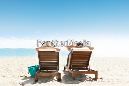 couple relaxing on deck chairs at