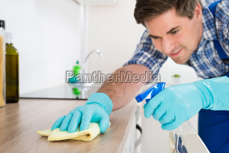 worker cleaning countertop with rag