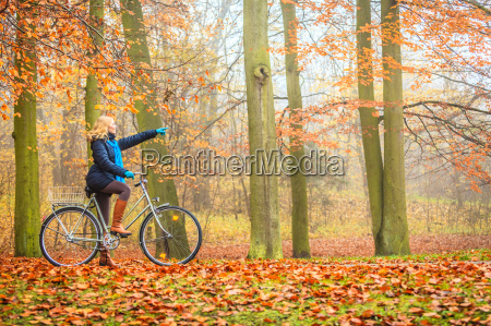 active woman riding bike in autumn