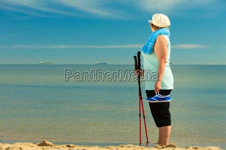 active nordic senior woman walking on