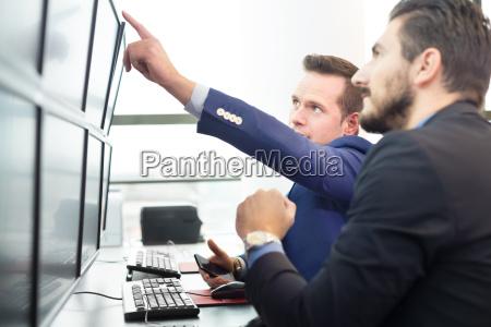 stock traders looking at computer screens