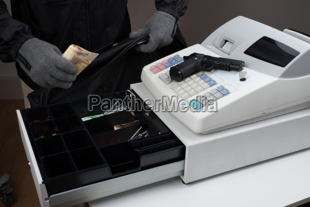 robber taking money from cash register