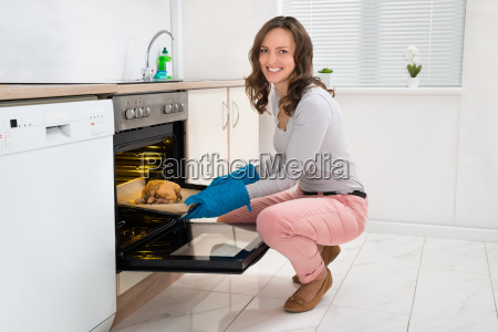 woman cooking chicken in oven