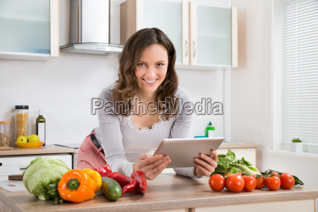 woman with digital tablet and vegetables