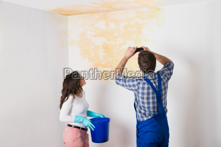 handyman with woman photographing ceiling at