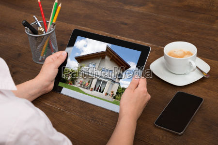 businessperson looking at house photo on