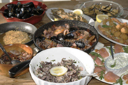 a buffet of dishes of fish