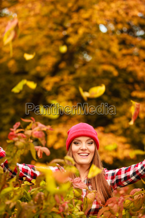 woman in autumn park throwing leaves