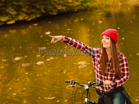 woman relaxing in autumnal park with