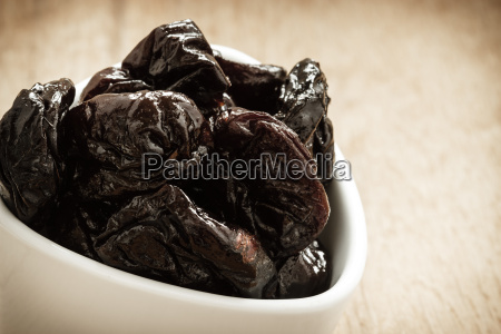 dried plums prunes in white bowl