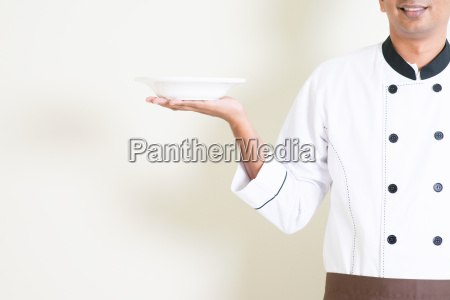 indian male chef in uniform holding