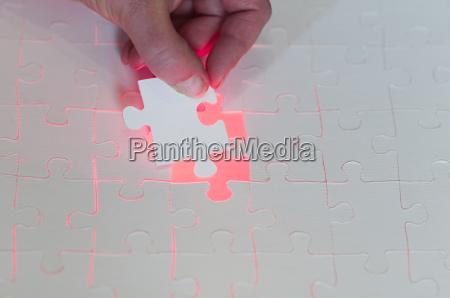 hand puts in last puzzle piece