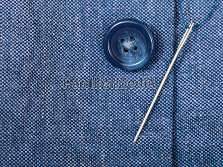 attaching of button to blue silk
