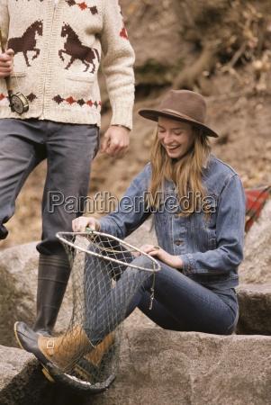 young couple in a forest fishing