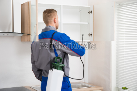 worker spraying insecticide on shelf