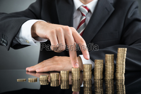 businessmans fingers walking on coins