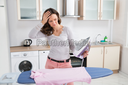 woman with electric iron and cloth