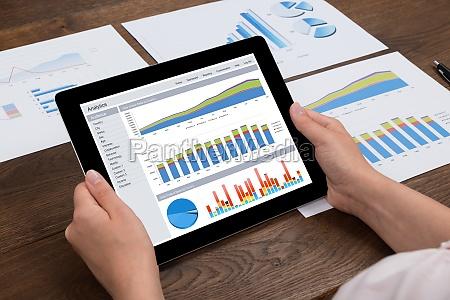 person analyzing financial statistics on digital