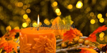 orange candle in autumn christmas setting