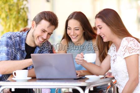 friends watching videos in a laptop