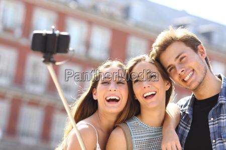 group of tourist friends taking selfie