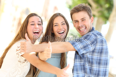 three happy teenagers laughing with thumbs