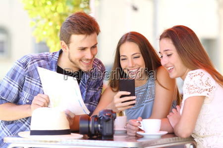 tourist friends planning vacation with gps