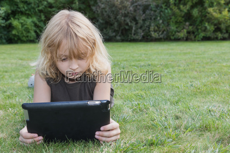 boy is looking to the tablet