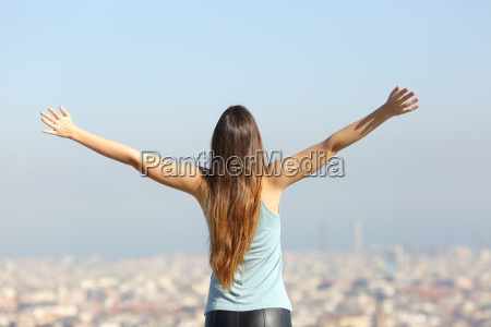 happy tourist woman raising arms looking