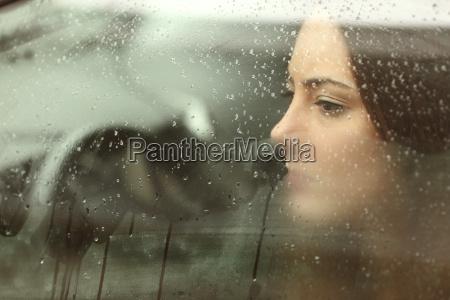 sad woman looking through a car