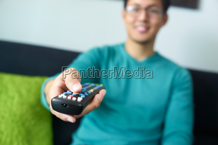 asian man watching tv changes channel
