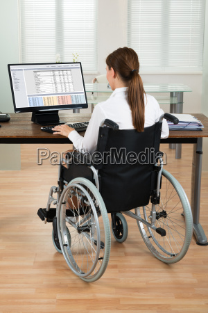 architect on wheelchair looking at blueprint