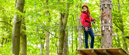 teenager maedchen klettert im klettergarten