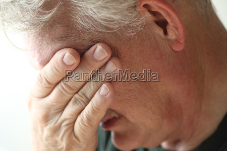senior man with hand over eyes
