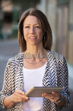 confident woman holding tablet