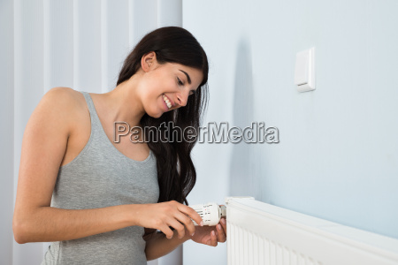 woman adjusting thermostat on radiator