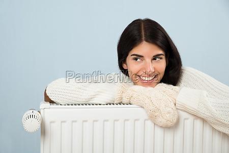 woman in sweater leaning on radiator