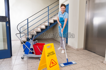 worker with cleaning equipments and wet