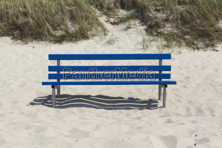 blue bench in beach sand