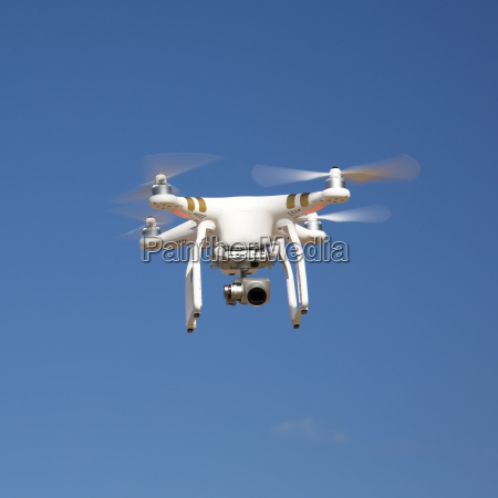 drone hovering against blue sky on