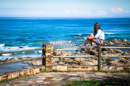 young woman sitting on bench facing