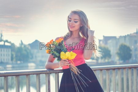 pretty woman with flowers leaning against