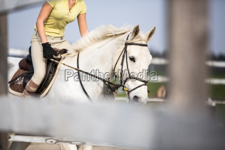 young woman show jumping with horse