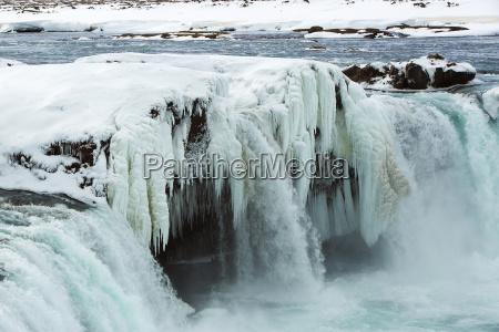 closeup of frozen waterfall godafoss iceland