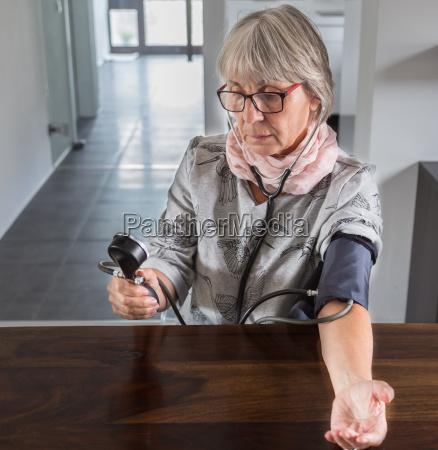 senior woman checks blood pressure at