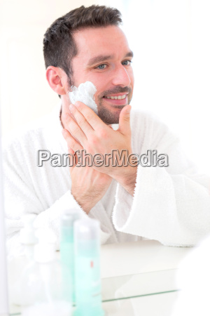 young attractive man shaving his beard