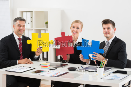 team of businesspeople holding jigsaw puzzle