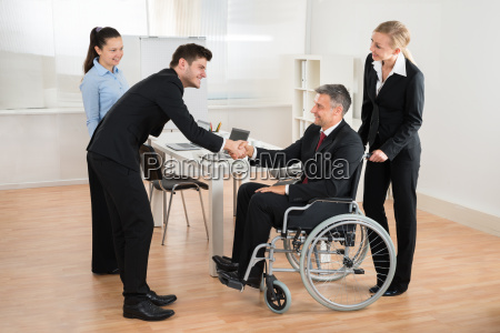 businessman in wheelchair shaking hands with