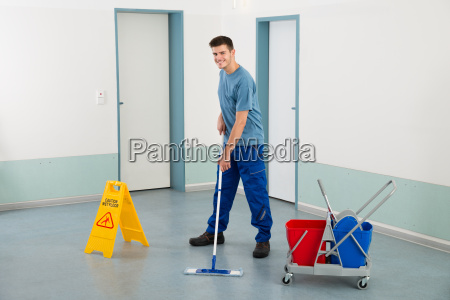 male worker with cleaning equipments mopping