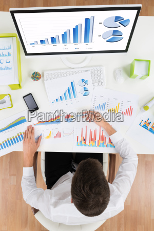 businessman analyzing graph on computer at